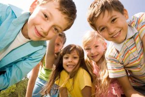 Fröhliche Kindergesichter schauen den Betrachter an