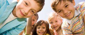 Fröhliche Kindergesichter schauen aus dem Bild heraus